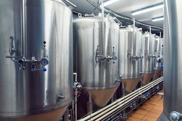 Линии металлических емкостей в современной пивоварне. цех с пивоварней. технологический процесс заваривания. способ производства пива. пивоварение. вид изнутри на современный пивзавод с бочками из нержавеющей стали.
