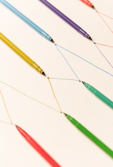 Линии, окрашенные красочными маркерами на белой бумаге