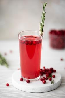 白いテーブルの上のガラス皿にローズマリーと蜂蜜とリンゴンベリージュース Premium写真