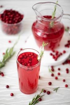 白いテーブルの上のガラス皿にローズマリーと蜂蜜とリンゴンベリージュース