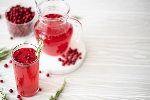 Брусничный сок с розмарином и медом в стеклянной посуде на белом столе