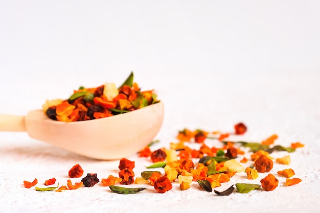 Lingonberry, sea buckthorn, cranberry and lingonberry leaves on wooden spoon