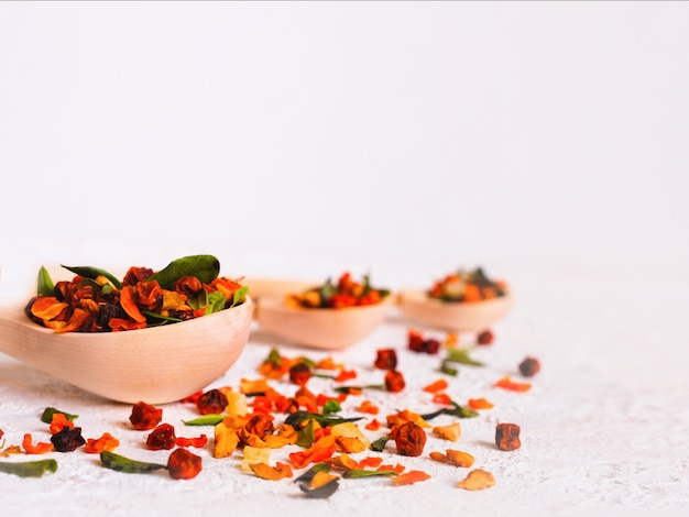 Lingonberry, sea buckthorn, cranberry and lingonberry leaves on wooden spoons