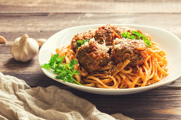 Linguine pasta with meatballs in tomato sauce and parsley on rustic wooden background
