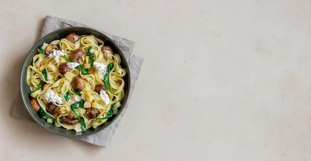 きのこ、ホワイトチーズ、ほうれん草、にんにくのリングイネパスタ。健康的な食事。ベジタリアンフード。ダイエット。