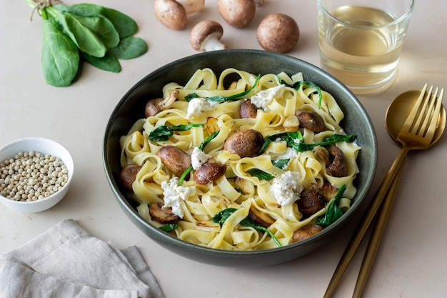 Linguine pasta with mushrooms, white cheese, spinach and garlic. healthy eating. vegetarian food. diet.