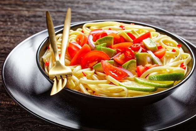 暗い木製のテーブルの上の黒いボウルに刻んだ唐辛子と赤玉ねぎを振りかけたアボカド、トマト、ライムのリングイネ、上からの水平方向のビュー、クローズアップ