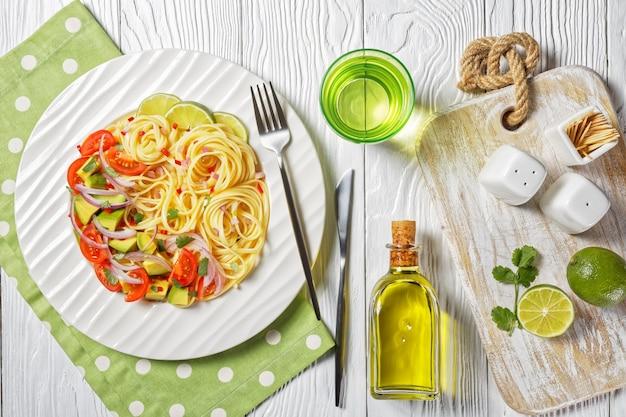 アボカド、トマト、ライムを刻んだ唐辛子と赤玉ねぎを木製のテーブルの白いプレートに振りかけたリングイネ、上からの水平方向のビュー、フラットレイ