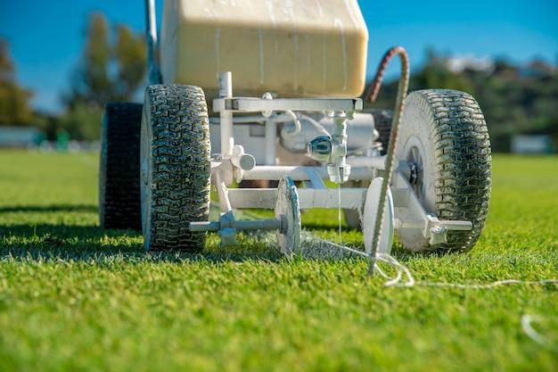 Выравнивание футбольного поля белой краской на траве