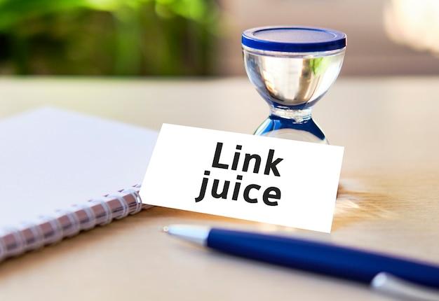 Seoウェブサイトのリンクジュース-白いノートと砂時計、花の葉のビジネスコンセプトテキスト