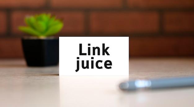 リンクジュース-ホワイトリストにあるビジネスコンセプトのテキストとペンと後ろに花が付いた黒いポット