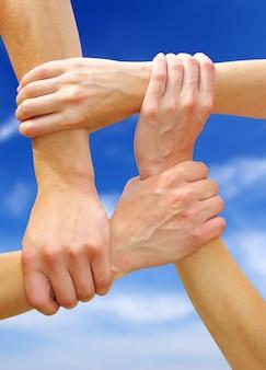 Linked hands on a sky background symbolizing teamwork and friendship