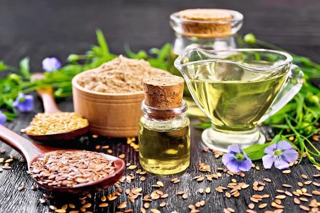 2つのガラス瓶に亜麻仁油とスプーンに白と茶色の亜麻仁、ボウルに小麦粉、暗い木の板の背景に葉と花のソースボート