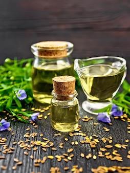 Льняное масло в двух стеклянных банках и соусник с семенами, цветы льна на фоне деревянной доски