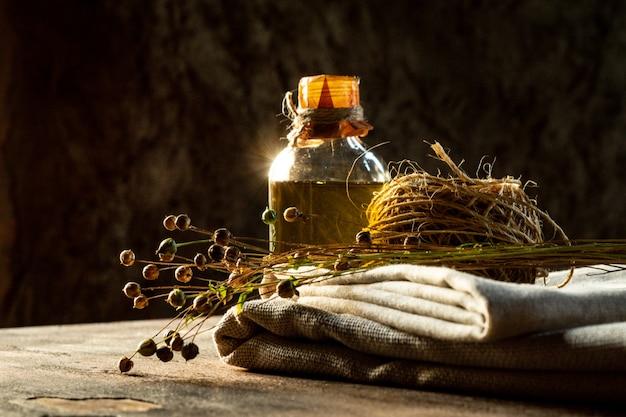 Льняное масло, льняная ткань, веревка и сухие растения льна