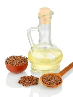 Linseed oil with flax seeds on white background close-up