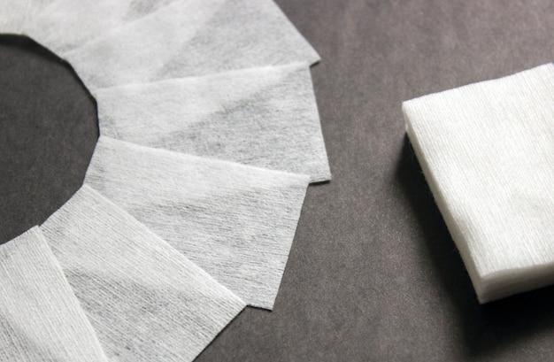 Безворсовые салфетки на темном фоне. профессиональные инструменты для ухода за ногтями для маникюра. снятие лака небольшой нейл-арт и маникюрный бизнес. инструмент для снятия лака и обезжиривания.