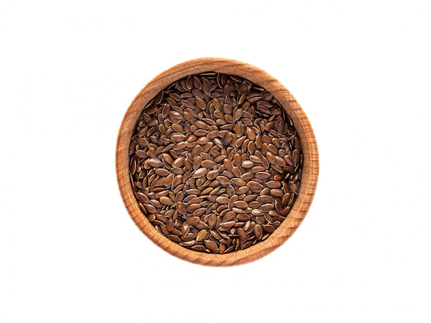 Linum seeds in a wooden cup on a white