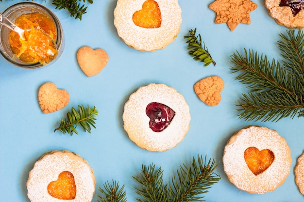 Linzer christmas or new year cookies filled with jam on blue paper background.