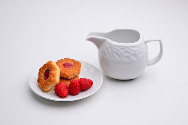 Печенье linzer с сердечком с малиновым вареньем белая тарелка с чашкой