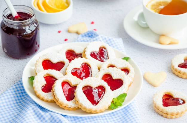 Linzer cookies with heart with raspberry jam and powdered sugar on a white plate with a cup of tea.
