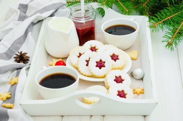 Рождественское печенье linzer заполнено с клубничным вареньем на белой тарелке на подносе с двумя чашками кофе.