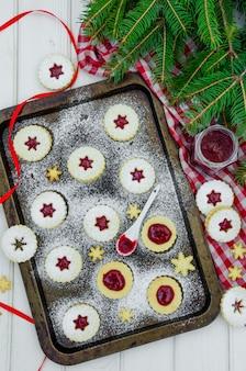 Домашнее рождественское печенье linzer с клубничным вареньем на противне на белой древесине