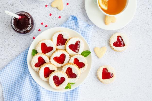 Печенье linzer с сердцем с малиновым вареньем и сахарной пудрой на белой тарелке с чашкой чая.
