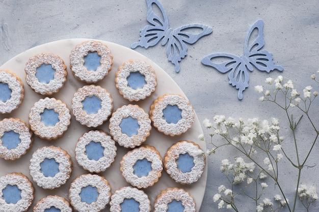 Вид сверху цветочного печенья linzer с голубой глазурью, украшенной цветами и бабочками