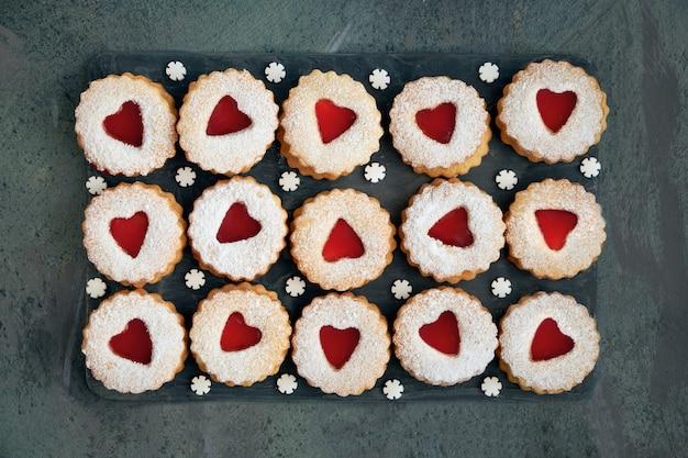 Взгляд сверху традиционного печенья linzer рождества с красным вареньем на темноте