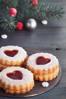 Крупный план традиционного рождественского печенья linzer, наполненного красным вареньем, темно-серого цвета с рождественскими украшениями