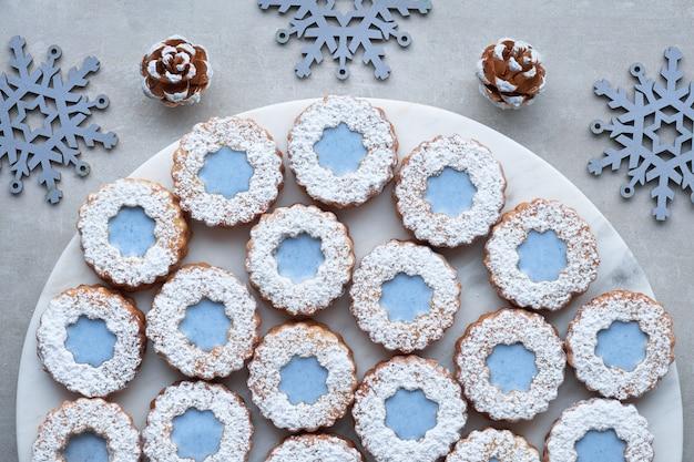 Бело-голубое цветочное печенье linzer на светлой каменной поверхности с зимними украшениями
