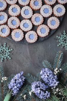 Цветочное печенье linzer с голубой глазурью на темном фоне, украшенное ягодами и снежинками