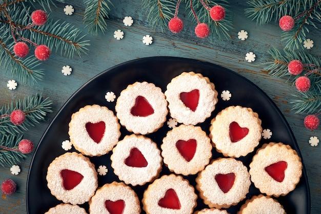 Вид сверху традиционного рождественского печенья linzer с красным вареньем на темном фоне