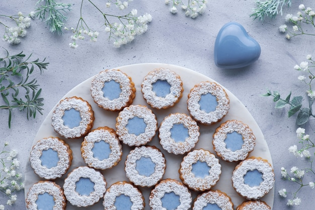Вид сверху цветочного печенья linzer с голубым остеклением на голубом, украшенном белыми цветами и керамическим сердцем