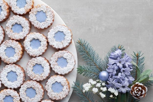 Цветочное печенье linzer с голубой глазурью на светлом бетоне, украшенное голубыми цветами гиацинта, еловыми ветками и зеленью