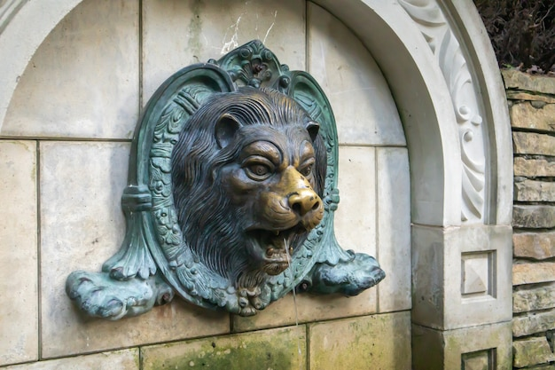 벽에 사자 머리 분수입니다. 사자 모양의 치장 벽토가 있는 빈티지 벽돌 벽 텍스처입니다. 성형된 사자의 얼굴에 물을 뿌립니다. 부조 사자 분수.
