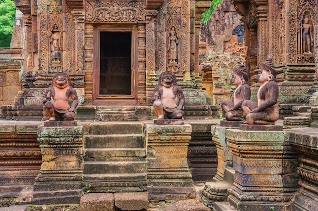 Lion and monkey gardians carvings at banteay srei red sandstone temple, cambodia