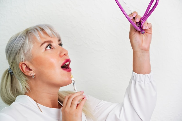 Увеличение губ и омоложение лица у женщин молодая жизнерадостная женщина делает инъекции губ красотой ...