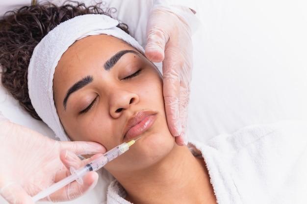입술확대술. 히알루론산 주사를 받는 아름다운 젊은 여성의 입. 섹시 한 여성 입술에 대 한 미용 절차를 하 고 미용사 손의 근접 촬영. 미용 치료. 높은 해상도