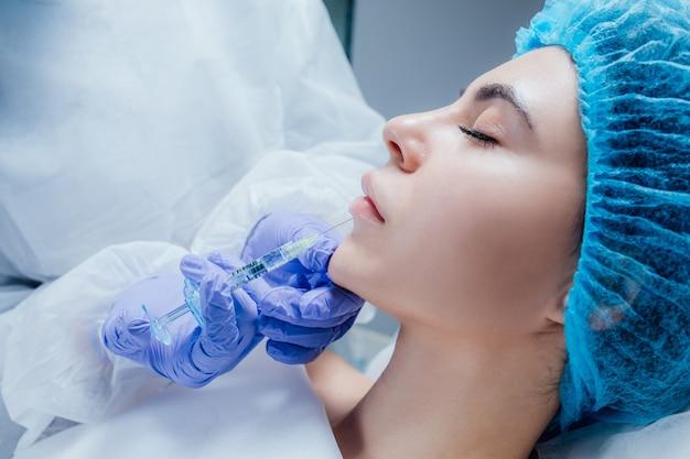 입술 확대. 히알루 론산 주사를받는 아름다운 젊은 여성의 입
