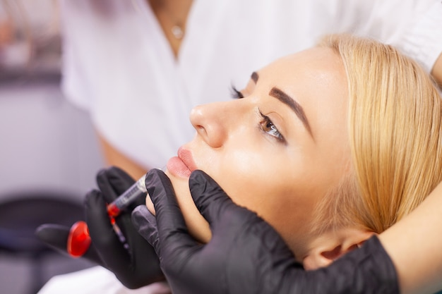 Lip augmentation in cosmetology clinic, beautiful woman getting beauty injection for lips