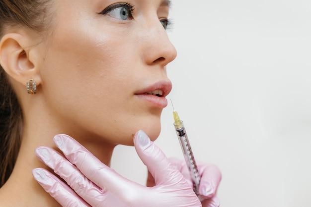 Процедура увеличения губ для молодой красивой девушки. косметология.