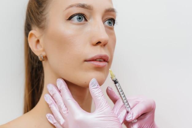Процедура увеличения губ для красивой молодой женщины