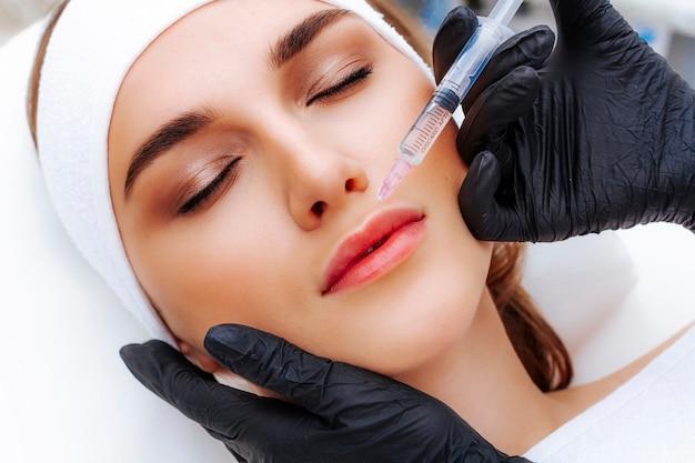 Процедура увеличения губ гиалуроновой кислотой. косметолог протыкает губы иглой. подкожная инъекция.