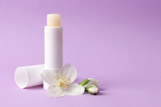 Lip balm and flowers on a colored background close-up with a place to insert text. high quality photo