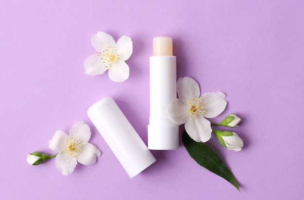 Lip balm and flowers on a colored background closeup