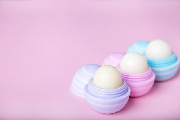 ピンクの背景にリップクリーム。保護肌。リップケアのコンセプト。コピースペース
