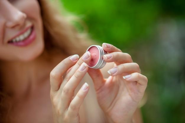 립밤. 그녀의 손에 립밤을 들고 웃 고 예쁜 젊은 여자