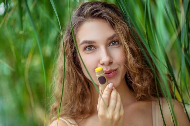 Lip balm. pretty young woman holding a stick of lip balm